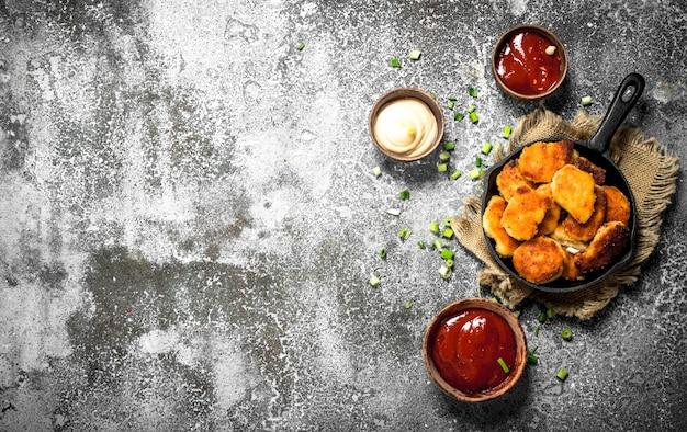 Nuggetsy z kurczaka na patelni z różnymi sosami. na rustykalnym tle.