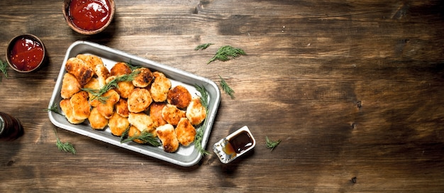 Nuggetsy z kurczaka na stalowej tacy z sosem. na drewnianym stole.