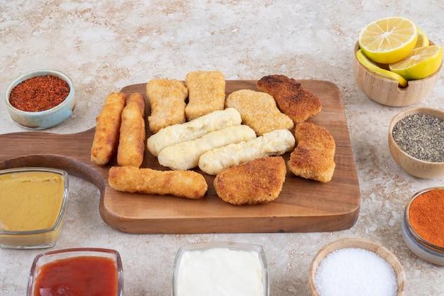 Nuggetsy z kurczaka, paluszki serowe i smażone kiełbaski z różnymi sosami i przyprawami.