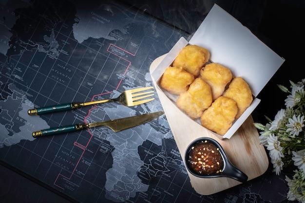 Nuggetsy z kurczaka. smażone jedzenie o złocistożółtym kolorze. czarne tło.