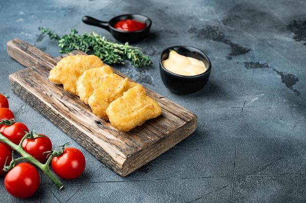 Nuggetsy z kurczaka smażone na szarym stole.