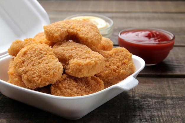 Nuggetsy z kurczaka w pudełku dostawy żywności z biało-czerwonym sosem na brązowym tle drewnianych. zbliżenie fast foodów