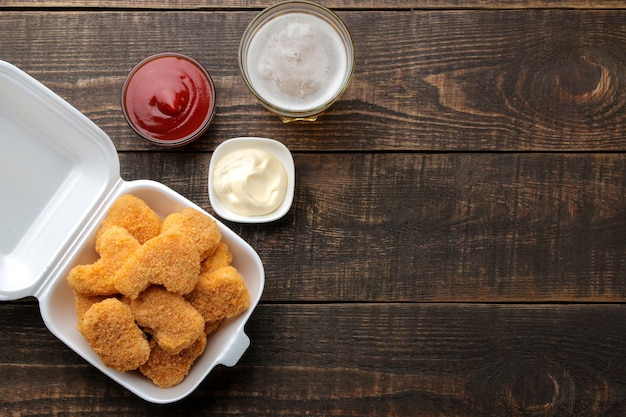 Nuggetsy z kurczaka w pudełku dostawy żywności z białym i czerwonym sosem i piwem na brązowym tle drewnianych. widok z góry fast food z miejscem na tekst