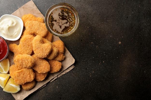 Nuggetsy z kurczaka z biało-czerwonym sosem i piwem i cytryną na brązowym tle. widok z góry fast food z miejscem na tekst
