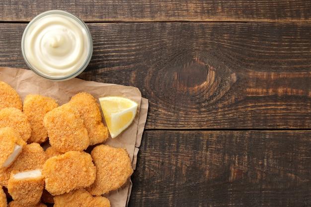 Nuggetsy z kurczaka z białym sosem na brązowym drewnianym tle. widok fast foodów z góry