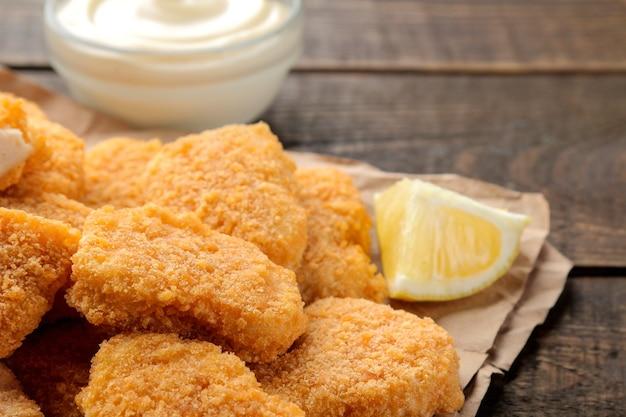 Nuggetsy z kurczaka z białym sosem na brązowym drewnianym tle. zbliżenie fast foodów