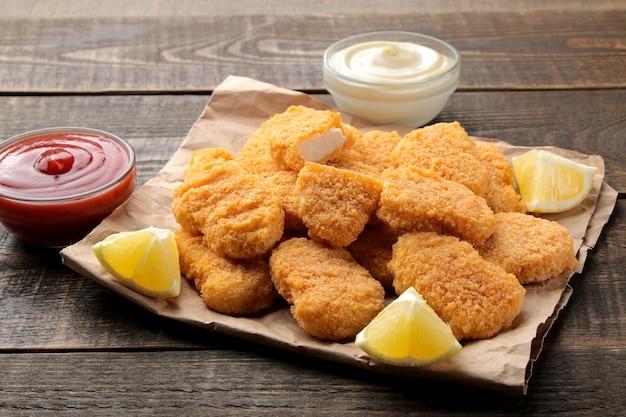 Nuggetsy z kurczaka z czerwono-białym sosem na brązowym drewnianym stole fast food
