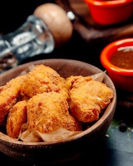 Nuggetsy z kurczaka z sosem barbecue na stole