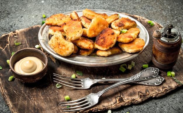 Nuggetsy z kurczaka z sosem serowym na desce. na rustykalnym tle.