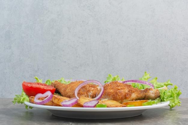 Nuggetsy z kurczaka ze smażonym ziemniakiem i cebulą na białym talerzu.