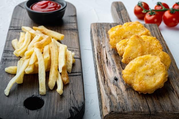 Nuggetsy z piersi kurczaka smażone na białym stole.