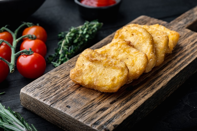 Nuggetsy z piersi kurczaka smażone na czarnym drewnianym stole.