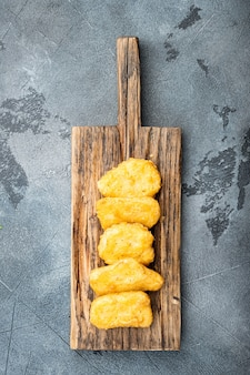 Nuggetsy z piersi kurczaka smażone na szarym stole, widok z góry.