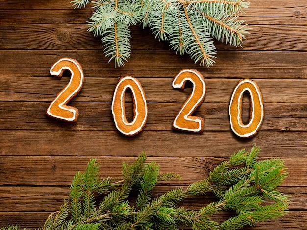 Numer 2020 wykonany z pierników na drewnianym. gałązki świerkowe. nowy rok