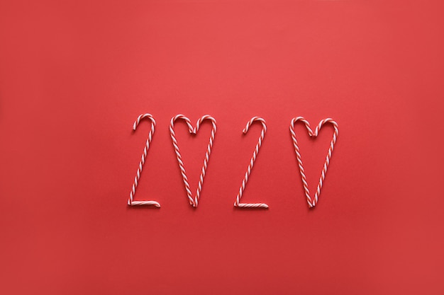 Numer 2020 wykonany z różnymi świątecznymi rożkami na czerwono. minimalny nowy rok. kreatywne płaskie świeckich tło.