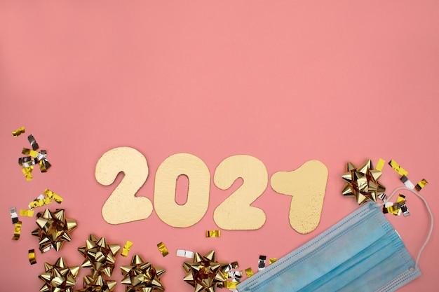 Numer 2021 na różowym tle ozdobionym złotym gwiaździstym konfetti