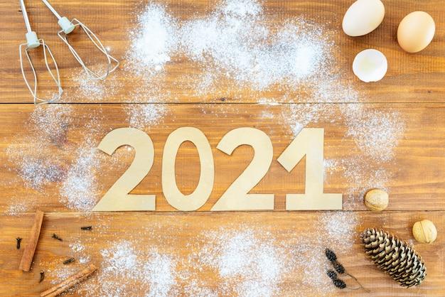 Numer 2021 wokół mąki, jajek i trzepaczki na brązowym drewnianym stole.