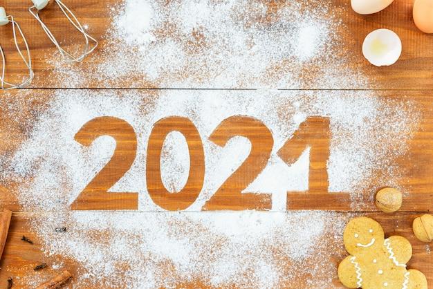 Numer 2021 wokół mąki, jajek, trzepaczki i przypraw na brązowym drewnianym stole.