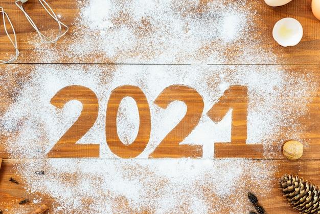 Numer 2021 wokół mąki, jajek, trzepaczki i przypraw na brązowym drewnie