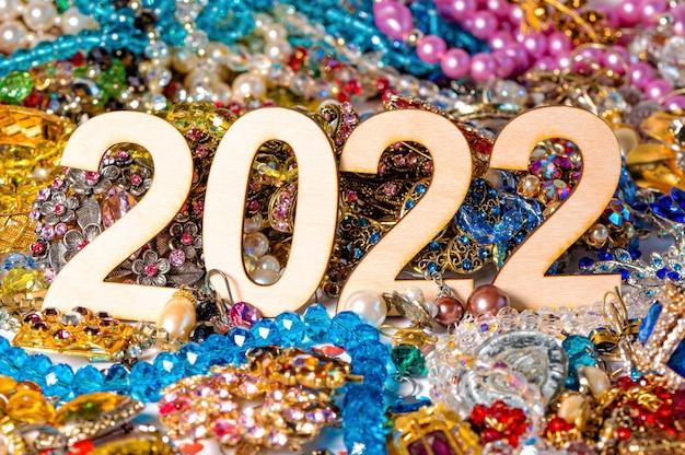 Numer 2022 na tle kolorowej biżuterii, koncepcja na początek nowego roku, zbliżenie
