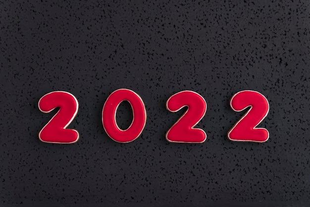 Numer 2022 nowy rok z czerwonego piernika na czarnym tle. widok z góry