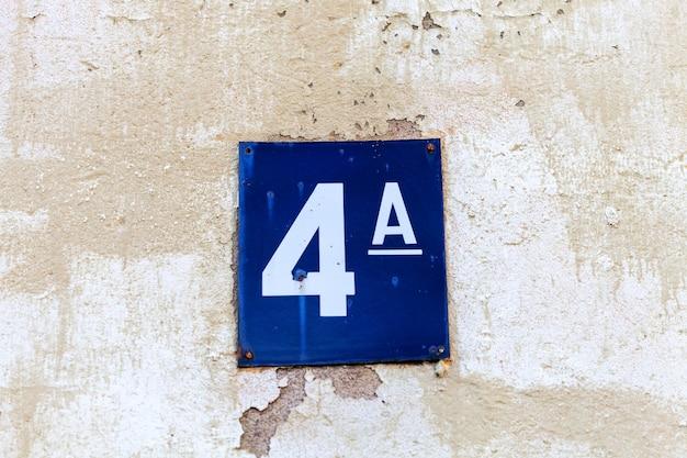 Numer 4 na kamiennej starej białej ścianie