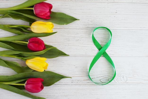 Numer 8 na 8 marca z bukietem tulipanów. międzynarodowy dzień kobiet