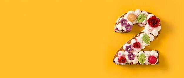 Numer dwa ciasto ozdobione kwiatami i makaronikami na żółtym tle panorama widok kopiowanie miejsca