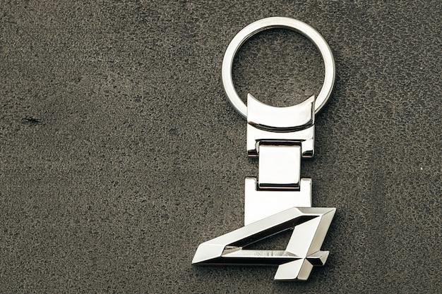 Numer metalu cztery kluczyk samochodowy na ciemnym tle betonu z bliska