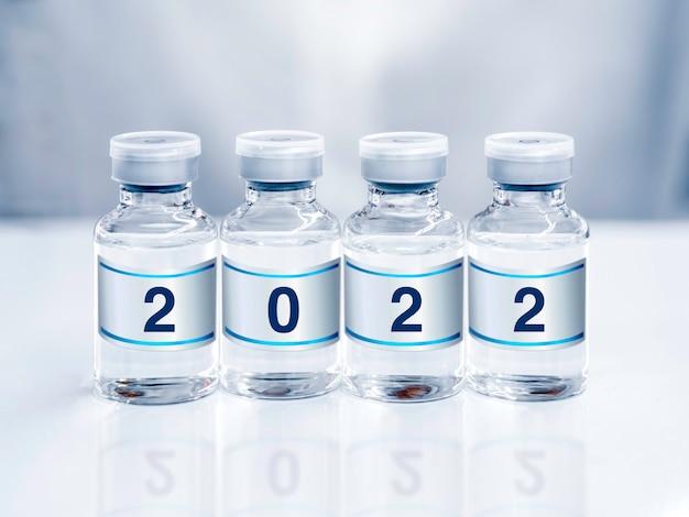 Numery roku 2022 na etykiecie na fiolkach ze szczepionkami w laboratorium. cztery szklane butelki z lekiem przeciwko wirusowi covid-19 na epidemię immunizacji koronawirusem. koncepcja szczepień.