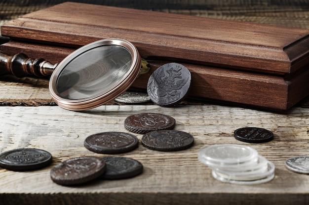 Numizmatyka. stare monety kolekcjonerskie na drewnianym stole. ciemne tło.