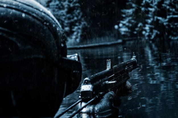 Nurek wojskowy wynurza się z wody i celuje z karabinu maszynowego