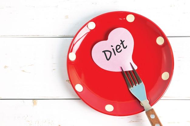 Nutowy papier z wiadomością dołączającą rozwidlać, na talerzu, na drewnianym tle. pojęcie diety opieki zdrowotnej.