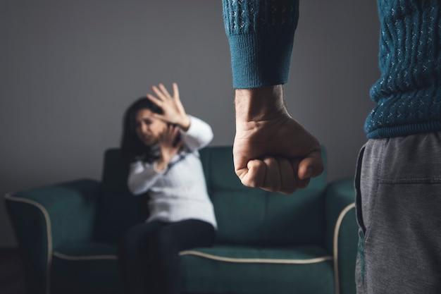 Nygry mężczyzna bije młodą smutną kobietę