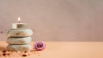 Oświetlona świeca na stos kamieni spa z soli himalajskiej i różowa róża na kolorowym tle