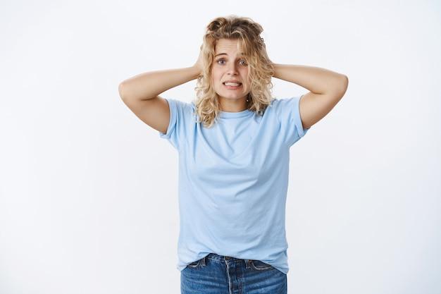 O boże, mam kłopoty. portret zmartwionej paniki, urocza głupia blondynka trzymająca się za ręce na głowie, ściskająca zęby i patrząca przerażona w kamerę, jako nieświadoma, co robić, czując się zdenerwowana i zmartwiona