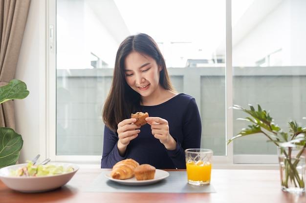 O koncepcji posiłku uśmiechnięta kobieta doceniając jej ulubione desery na stole w jadalni.