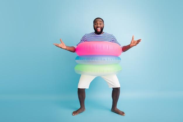 O mój boże, koleś, to ty? pełnowymiarowe zdjęcie pozytywny szalony boso amerykański facet afroamerykanin ciesz się wypoczynkiem wakacje mieć boje chcesz przytulić przyjaciela nosić kamizelkę w paski białe szorty izolowane niebieski kolor ściana