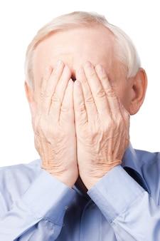 O mój boże! sfrustrowany starszy mężczyzna zakrywający twarz rękami, stojąc na tle bieli