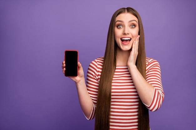O mój boże, spójrz na nowe urządzenie! zdziwiona zaskoczona dziewczyna trzyma telefon komórkowy obecna niesamowita promocja reklam pod wrażeniem krzyk wow omg nosić sweter odizolowany na fioletowej ścianie