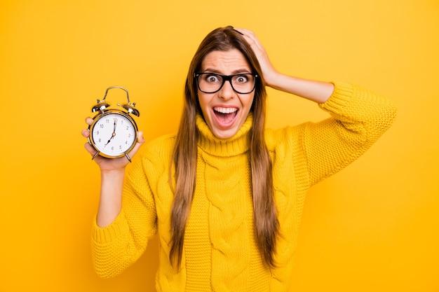 O mój boże, spóźniłem się! szalona sfrustrowana dziewczyna licealistka trzymaj zegar tęsknię za kursami akademickimi termin czasu krzyk niewiarygodny kołnierz nosić sweter z dzianiny izolowany żółty kolor ściana
