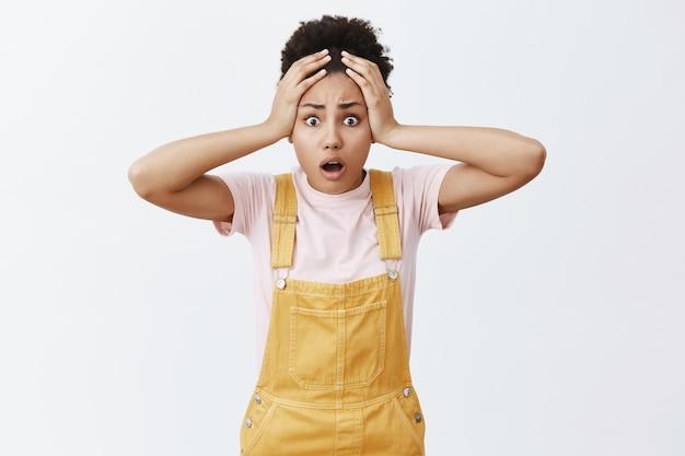 O nie, nie byłem przygotowany. zszokowana i nerwowa śliczna ciemnoskóra studentka w żółtym kombinezonie, trzymająca się za głowę i dysząca z przestraszoną twarzą, znajdująca się w rozpaczliwej sytuacji