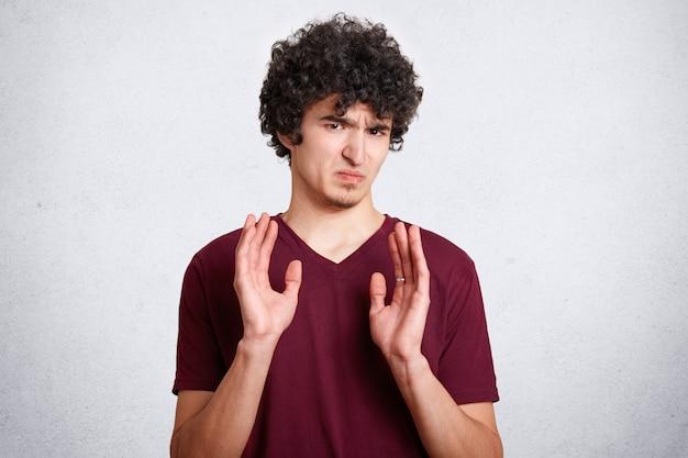O nie, nie przeszkadzaj mi! zirytowany mężczyzna w złym humorze o kruchych włosach, pokazuje gest odmowy, pozuje na białym tle