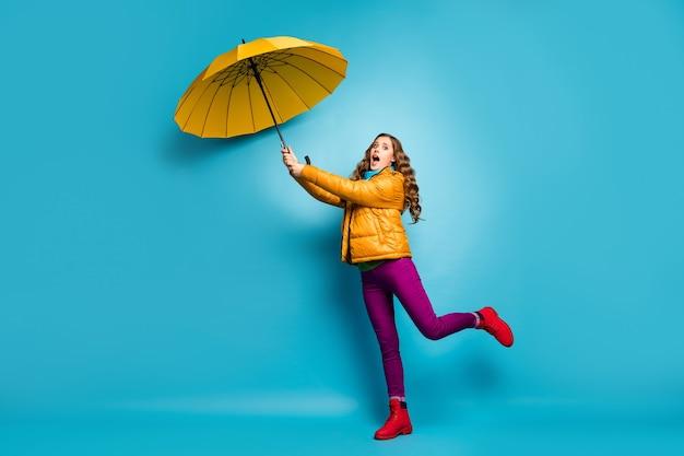 O nie! pełnowymiarowe zdjęcie profilowe szalonej zszokowanej kobiety trzymającej parasol latający w górę z wiatrem nosić żółty płaszcz szalik fioletowe spodnie czerwone obuwie izolowany niebieski kolor ściana