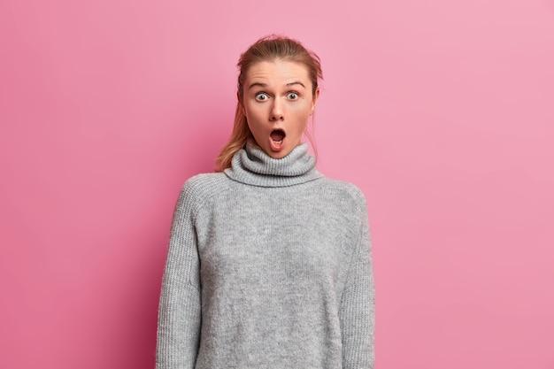 O nie! zszokowana młoda kobieta z opuszczoną szczęką, reaguje na coś zapierającego dech w piersiach, patrzy bez słowa, nosi ciepły szary sweter