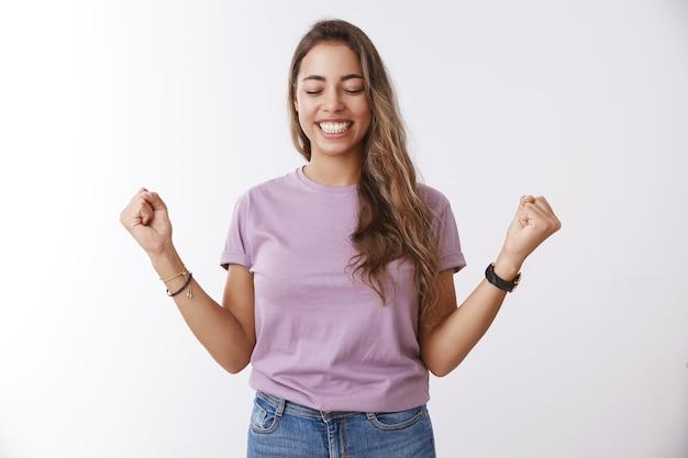 O tak wreszcie zwycięstwo. szczęśliwa ulga atrakcyjna urocza studentka zdobywająca stypendium uniwersyteckie podnosząca zaciśnięte pięści, ciesząca się sukcesem, świętująca zwycięstwo, osiągająca cel, uśmiechnięta