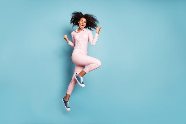 O tak! zdjęcie profilowe całego ciała niesamowitej uroczej ciemnoskórej kręconej kobiety skaczącej wysoko świętującej wielkie zwycięstwo nosić różowe spodnie koszulowe na białym tle na niebieskim tle