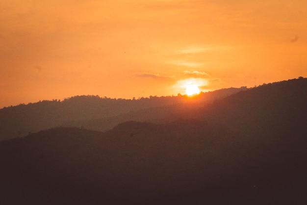 O zachodzie słońca górski krajobraz sylwetki. słońce za górami . zachód słońca nad górą.