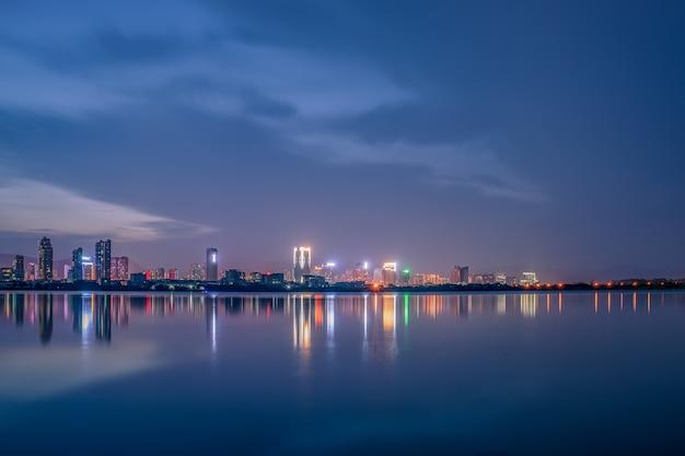 O zmierzchu jezioro odbija nocny widok miasta