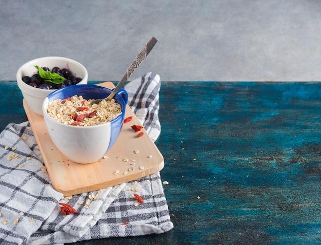 Oatmeal w filiżance z jagodami w pucharze na drewnianej desce